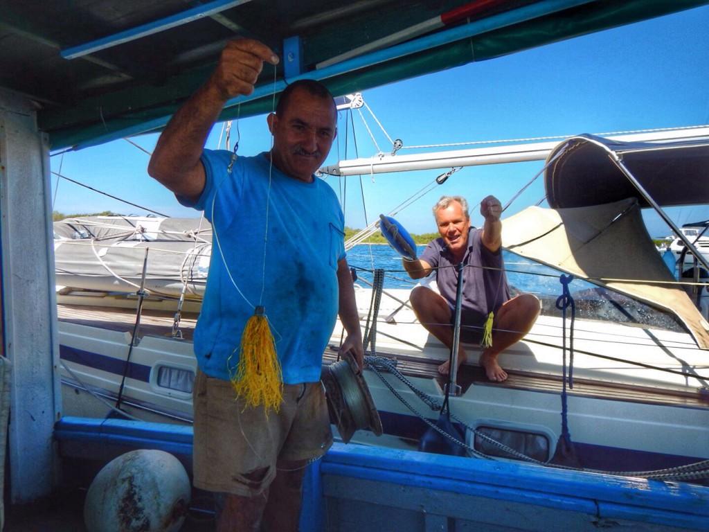 Voor vertrek vergelijkt Ben het visgerei met de vissers naast ons. Ze blijken precies dezelfde dubbele haak te hebben. Dit moet lukken!